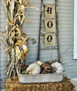 vintage hay bale fall porch with a rustic ladder with boo sign and dried cornstalks