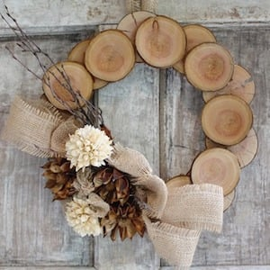 fall wood slice wreath with a burlap bow and pinecones