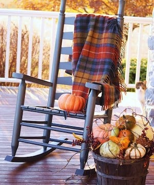 rocking chair on porch with fall tartan blanket and a barrel of pumpkins