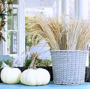 Chic Neutral Fall Porch with wicker basket of wheat and white pumpkins