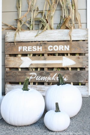 wood pallet fall sign with dried corn and white pumpkins