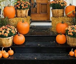 Fall Porch Stairs with mums, hay bales and various sized pumpkins