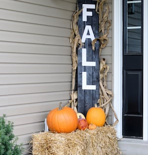 Fall Pallet Sign with pumpkins on top of hay bales
