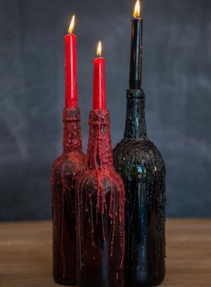 red Dripping Candles in black wine bottles halloween party centerpiece