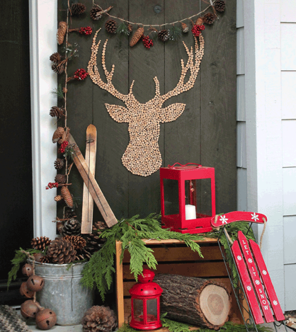 simple rustic winter front porch lanterns wood crate log galvanized bucket evergreen clippings old sleigh bells pinecones wood slice stag head