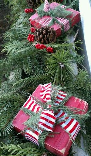 christmas window box source unknown pine garland or evergreen clippings wood blocks red spray paint christmas ribbon pinecones
