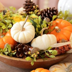 mini pumpkins, pinecones and greenery in a wooden bowl