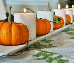 mini pumpkins and candles on a candle tray
