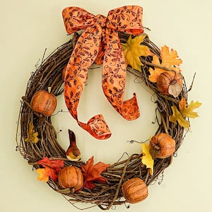 rustic fall grapevine wreath with mini pumpkins, fall leaf garland and a ribbon on top