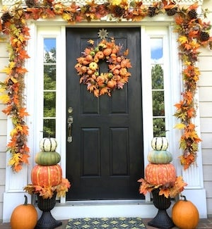 autumn porch with door fall leaves garland, pumpkin topiary and fall wreath