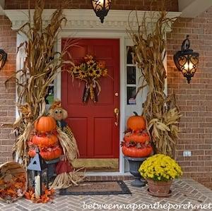 DIY Pumpkin Topiaries with dried cornstalks in the entryway
