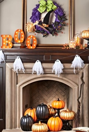 lassic Halloween Mantel with ghost garland and halloween wreath above fireplace