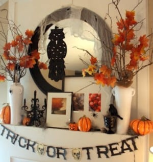 Fall Mantel with trick or treat garland and  fall branches in vases