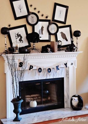 black and white Halloween decor with picture frames above mantel