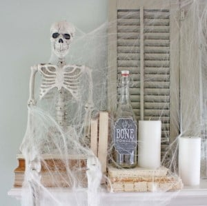 Ghostly Halloween Mantel Decor with spider webs and skeleton