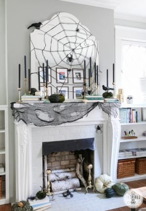 Spider web above the fireplace with black taper candles