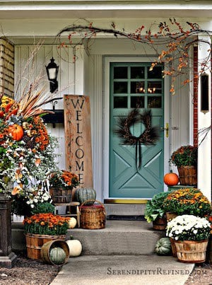 fall porch with orange turquoise and white mums, pumpkins