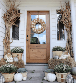 neutral fall porch decorating with dried corn, hay bales, white pumpkins and mums