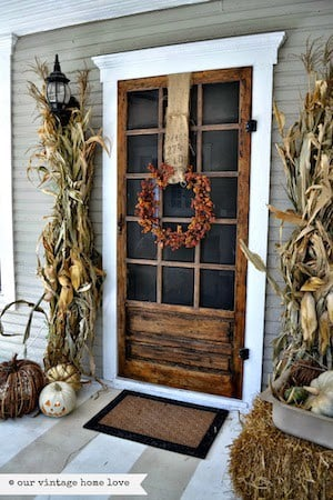 Vintage Fall Porch with dried corn stalks, hay bales and fall wreath