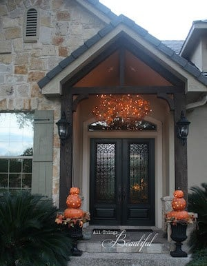 Fall Porch Lighting with pumpkin topiaries next to the front door