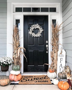 pumpkins and dried corn stalks on either side of the door