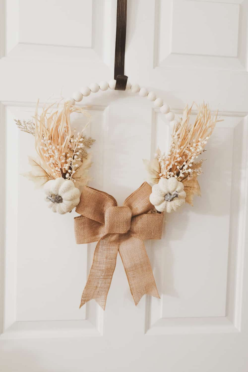 wood bead fall wreath that has a burlap bow on bottom with two neutral fall picks on the side