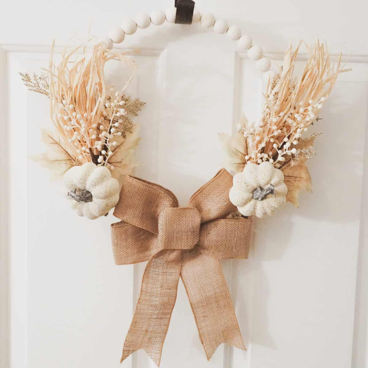 close up image of fall wood bead wreath with burlap, white pumpkins, raffia, berries and leaves